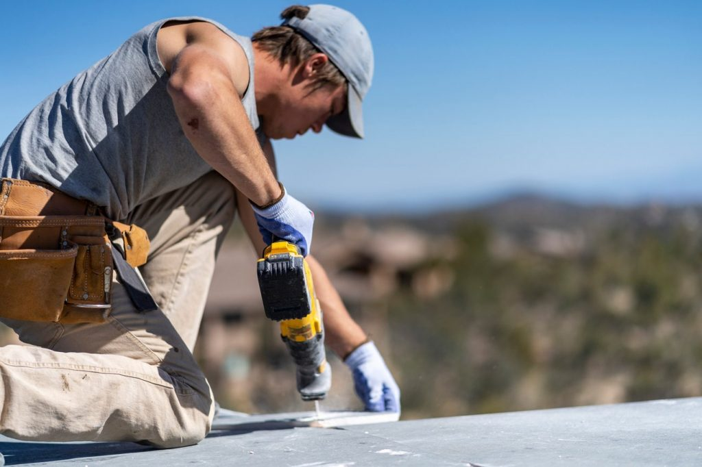 Employee of Heritage Roofing Contractor using A Drill On A Roof In Prescott, AZ
