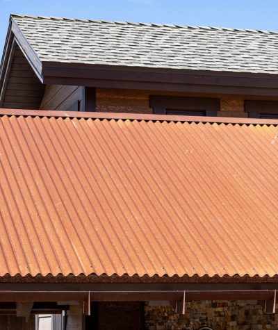 Closeup of Corrugated Rusted Iron Oxide Metal Metal Roof with Ultra GAF Shingles Roof (In the Background) by Heritage Roofing in Prescott, AZ
